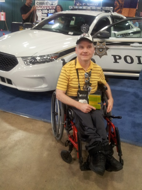 Man in Wheelchair in Front of a Police Car