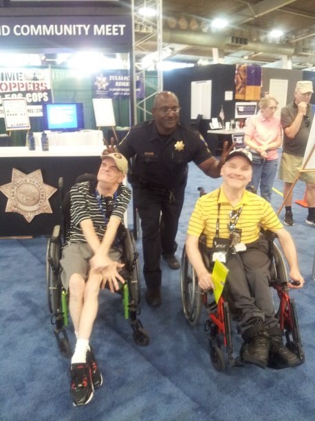 Police Officer Standing with 2 Men in Wheelchairs